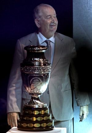 """FILE - In this Nov. 11, 2010 file photo, Julio Grondona, president of the Argentine Football Association, stands behind the Copa America trophy during the draw of the groups' ceremony in La Plata, Argentina. Grondona was hospitalized on Wednesday, July 30, 2014, said national football authorities, who said he was """"not feeing well."""" (AP Photo/Natacha Pisarenko, File)"""