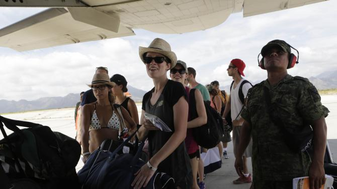 Stranded tourists wait before boarding a plane of the Mexican Army in San Jose del Cabo, that will transport them to Mazatlan international airport, after Hurricane Odile hit in Baja California