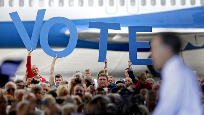 """Crowd members hold up a sign reading """"vote"""" as Republican presidential candidate, former Massachusetts Gov. Mitt Romney speaks during a campaign event at the Orlando Sanford International Airport, Monday, Nov. 5, 2012, in Sanford, Fla. (AP Photo/David Goldman)"""