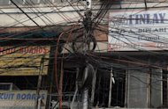 An electric pole is wrapped in wires in Kolkata. A massive power failure hit India for the second day Tuesday as three national grids collapsed, blacking out more than half the country in an unprecedented outage affecting over 600 million people