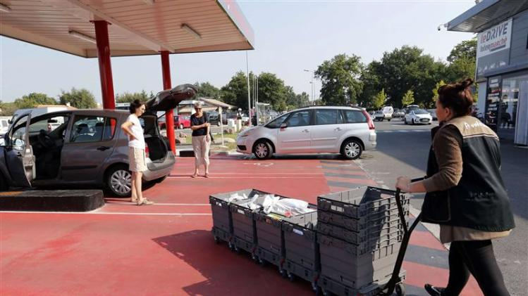 An employee pushes a caddy with groceries at a click and collect unit at an Intermarche supermarket in Lanton