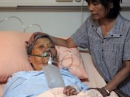 Wang Ho-shou, 94 is cared for by a member of her family a fire at a hospital in Tainan, southern Taiwan on October 23, 2012. Fire officials have said the blaze possibly started in a storage room on the second floor of the five-floor building mainly housing bed-ridden seniors