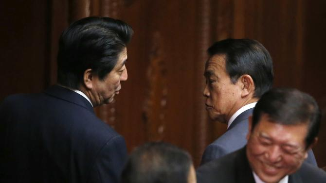 Japan's Prime Minister Shinzo Abe talks with Finance Minister Taro Aso after the dissolution of lower house was announced at the Parliament in Tokyo