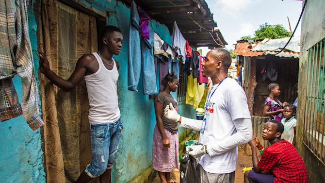 A health worker volunteer talks with a resident on how to prevent and identify the Ebola virus in others, and distributes bars of soap in Freetown, Sierra Leone, Saturday, Sept. 20, 2014. Thousands of health workers began knocking on doors across Sierra Leone on Friday in search of hidden Ebola cases with the entire West African nation locked down in their homes for three days in an unprecedented effort to combat the deadly disease. (AP Photo/Michael Duff)