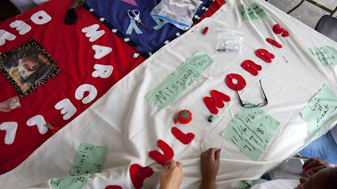 Cole Stone-Freisina, 16, left, of Atlanta, and Stephanie Laster, right, with the NAMES Project, works on a new panel to add to the AIDS Memorial Quilt, on the National Mall in Washington, on Saturday, July 21, 2012. (AP Photo/Jacquelyn Martin)
