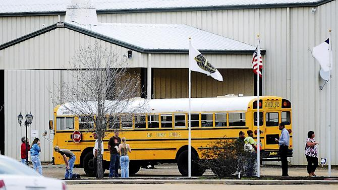 In this Tuesday, Jan 29, 2013 photo, residents look over the school bus where a shooting occurred near Destiny Church along U.S. 231, just north of Midland City, Ala. on Tuesday. Police, SWAT teams and negotiators were at a rural property where a man was believed to be holed up in a homemade bunker Wednesday, HAN 30, 2013 after fatally shooting the driver of a school bus and fleeing with a 6-year-old child passenger, authorities said. The man boarded the stopped school bus in the town of Midland City on Tuesday afternoon and shot the driver when he refused to let the child off the bus. The bus driver died. (AP Photo/The Dothan Eagle, Danny Tindell)