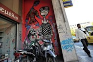 <p>A man walks past graffiti related to the economic crisis in central Athens on June 21. Leaders of the eurozone's four biggest economies gather in Rome Friday to thrash out ideas to tackle the debt crisis, with calls for the bloc's bailout fund to intervene on bond markets set to top the agenda.</p>