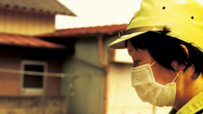 "In this image made from a scene from the film ""Fukushima: Memories of the Lost Landscape"" released by Yojyu Matsubayashi, Kyoko Tanaka, a city council member of Minami Soma, patrols in the deserted town after evacuation of the residents, on April 3, 2011. Japanese film director Matsubayashi took a more standard documentary approach for his ""Fukushima: Memories of the Lost Landscape,"" interviewing people who were displaced in the Fukushima town of Minami Soma. He followed them into temporary shelters in cluttered gymnasiums and accompanied their harried visits to abandoned homes with the gentle patience of a video-journalist. The March 2011 catastrophe in Japan has set off a flurry of independent films telling the stories of regular people who became overnight victims, stories the creators feel are being ignored by mainstream media and often silenced by the authorities. (AP Photo/Yojyu Matsubayashi) MANDATORY CREDIT, EDITORIAL USE ONLY"