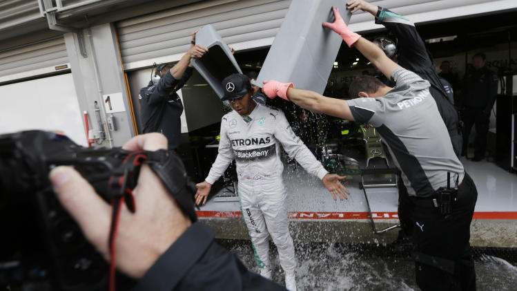 Technicians dump a bucket of ice water on Mercedes driver Lewis Hamilton of Britain to complete the Ice Bucket Challenge in support of the ALS Association which is raising funds in its battle to cure Lou Gehrig's disease, at the end of the first free practice at the Spa-Francorchamps circuit, Belgium, Friday, Aug. 22, 2014. The Belgium Formula One Grand Prix will be held on Sunday. The idea behind the challenge is to pour a bucket of ice cold water over yourself and to donate a sum of money to charity at the same time, or pay more to avoid doing the challenge. (AP Photo/Luca Bruno)