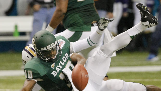 Baylor quarterback Robert Griffin III fumbles the ball as he is sacked by Washington's Andrew Hudson, rear, during the first half of the Alamo Bowl college football game, Thursday, Dec. 29, 2011, at the Alamodome in San Antonio. Washington recovered the ball. (AP Photo/Darren Abate)