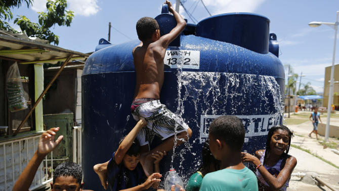 "Children play under the water that they manage to spill over from a water tank, to cool off from the summer heat, at the Alemao Complex slum in Rio de Janeiro, Brazil, Thursday, Jan. 29, 2015. State Environment Secretary Andre Correa acknowledged the region is ""experiencing the worst water crisis in its history,"" but said water provisioning would continue as normal through July, even in the worst-case scenario of continued drought over the coming weeks and months. (AP Photo/Leo Correa)"