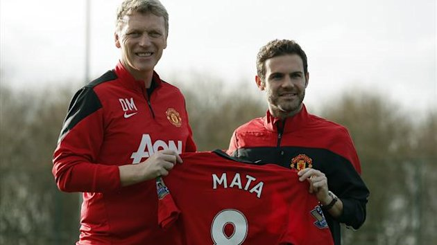Manchester United's new signing Juan Mata (R) holds a club shirt with club manager David Moyes during a photocall at the club's Carrington training complex in Manchester, northern England, January 27, 2014. (Reuters)