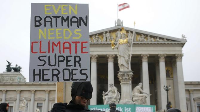 A protester dressed as Batman demonstrates outside Austrian Parliament during a rally held the day before the start of the Paris Climate Change Summit in Vienna