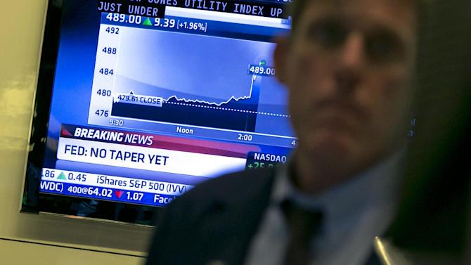A television monitor on the floor of the New York Stock Exchange shows the decision of the Federal Reserve, Wednesday, Sept. 18, 2013. The Federal Reserve has decided against reducing its stimulus for the U.S. economy, saying it will continue to buy $85 billion a month in bonds because it thinks the economy still needs the support. (AP Photo/Richard Drew)