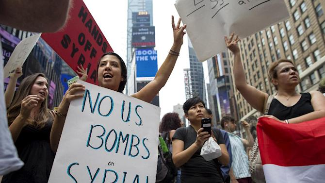Rachel Lee Richards of New York. left, stands with opponents of a United States military strike against Syria as she and others protest at Times Square in New York Saturday, Aug. 31, 2013. (AP Photo/Craig Ruttle)