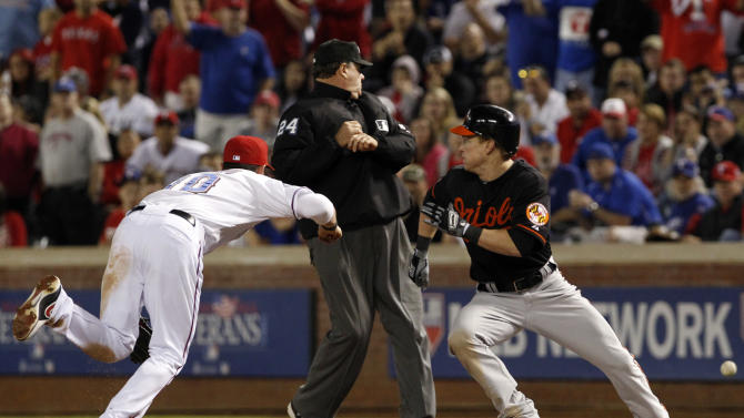 A throwing error by Texas Rangers pitcher Derek Holland gets past Michael Young (10), allowing Baltimore Orioles' Nate McLouth to advance to second during the seventh inning of an American League wild-card playoff baseball game Friday, Oct. 5, 2012, in Arlington, Texas. (AP Photo/LM Otero)