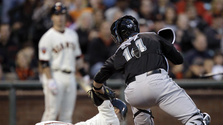 San Francisco Giants center fielder Andres Torres (56) scores past Florida Marlins catcher John Buck (14) as Torres ran from third base during a rundown after a strikeout by Aubrey Huff during the third inning of a baseball game in San Francisco, Wednesday, May 25, 2011. (AP Photo/Marcio Jose Sanchez)