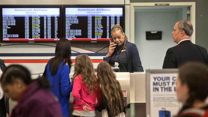 An American Airlines ticket agent talks on the phone while assisting passengers at Hartsfield-Jackson airport, Tuesday, April 16, 2013, in Atlanta. American Airlines flights across the country are grounded because of computer problems. American Airlines spokesman Kent Powell said Tuesday that the airline is trying to resolve the issues as quickly as it can. (AP Photo/David Goldman)