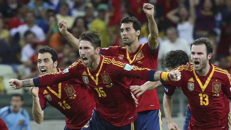 Spain's Sergio Ramos, front, and teammates Sergio Busquets, left, Juan Mata, right, and Alvaro Arbeloa , back, celebrate after defeating Italy in a penalty shootout during the soccer Confederations Cup semifinal match at Castelao stadium in Fortaleza, Brazil, Thursday, June 27, 2013. (AP Photo/Eugene Hoshiko)