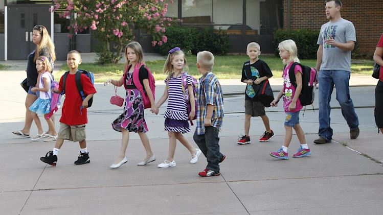 Students arrive for the first day of school for Plaza Towers Elementary school in their temporary location at Central Jr. High school in Moore, Okla., Friday, Aug. 16, 2013. The Briarwood and Plaza Towers elementary schools were destroyed when an EF5 twister hit Moore on May 20. (AP Photo/Sue Ogrocki)