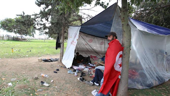 Unemployed Tunisians rest in a tent during a protest in Tunis