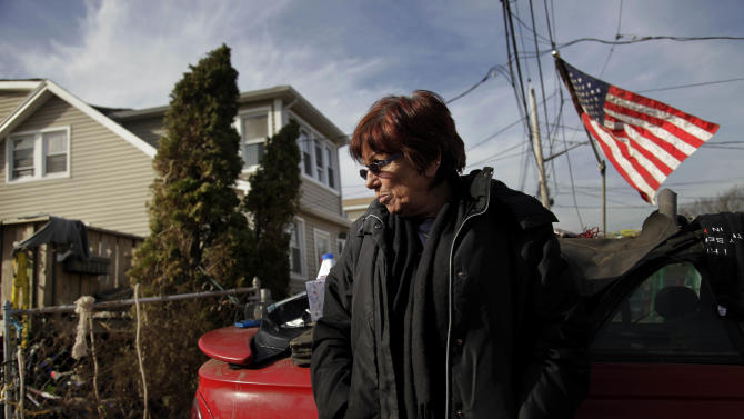 "In this Tuesday, Nov. 20, 2012 photo, Marge Gatti stands in front of her home, which was damaged by Superstorm Sandy, in the Midland Beach section of the Staten Island borough of New York. Of all things material, Gatti has nothing. And yet, on Thanksgiving Day, she will be counting her blessings this year. ""My sons are alive. They were trapped here,"" says Gatti, 67, who lived in this beige-colored home down the block from the Atlantic Ocean for 32 years. (AP Photo/Seth Wenig)"