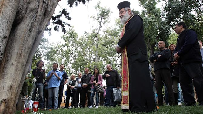 A Greek Orthodox priest holds a memorial service at the site where an elderly man fatally shot himself at Athens' main Syntagma square, on Wednesday, April 4, 2012. The Greek pensioner picked the busiest public area in Athens to shoot himself dead on Wednesday, leaving a note which police said linked his suicide with the country's acute financial woes. (AP Photo/Thanassis Stavrakis)