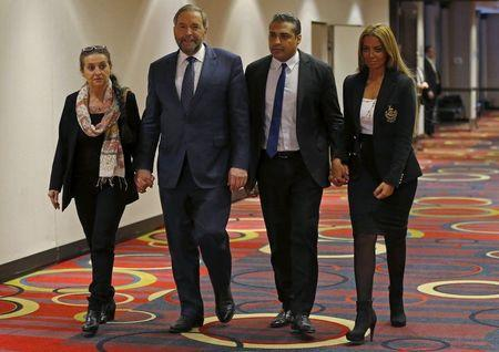 Canada's New Democratic Party leader Thomas Mulcair and his wife Catherine walk to a news conference with freed Al Jazeera journalist Mohamed Fahmy and wife Marwa Omara in Toronto