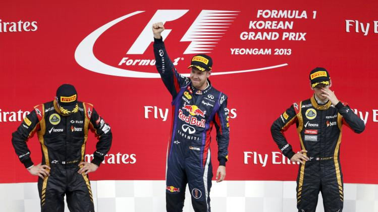 Winner Red Bull Formula One driver Vettel celebrates beside second placed Lotus Formula One driver Raikkonen and third placed Lotus Formula One driver Grosjean after the Korean F1 Grand Prix in Yeongam