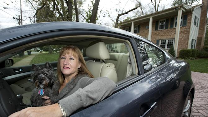 """In this photo taken Nov. 2, 2012, Diane Spitaliere and her pet dog Izzie sit in her car outside her house in Alexandria. Baby boomers, that giant population bubble born between 1946 and 1964, started driving at a young age and became more mobile than any generation before or since. Spitaliere, a 58-year-old who recently retired after working 38 years at the Federal Aviation Administration, said the idea of moving to a retirement or assisted living community """"is just very unappealing to me.""""    (AP Photo/Manuel Balce Ceneta)"""