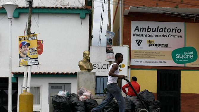 A man pushes a cart past an electoral poster of Miranda State's Gov. Henrique Capriles at the neighborhood of Petare in Caracas, Venezuela, Monday, Dec. 17, 2012.  Smarting after a bruising loss in state elections, Venezuela's opposition will now be forced to reassess its strategy and rebuild quickly to prepare for presidential elections that many expect could be called to replace ailing leftist President Hugo Chavez.(AP Photo/Fernando Llano)