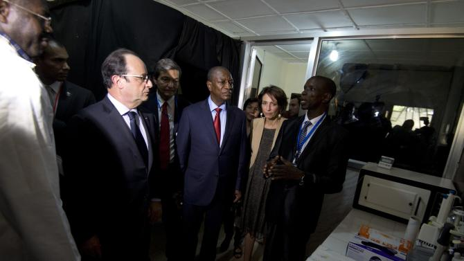French President Hollande and Guinea's President Alpha Omar Conde listen to a doctor during a visit the French Pasteur Institute laboratory at the Donka Hospital in Conakry