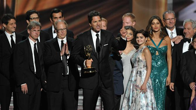 """Steven Levitan, center, and the cast and crew of """"Modern Family"""" accept the outstanding comedy series award at the 64th Primetime Emmy Awards at the Nokia Theatre on Sunday, Sept. 23, 2012, in Los Angeles. (Photo by John Shearer/Invision/AP)"""