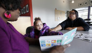 In this photo taken Dec. 8, 2011, Taliyah Garrett, 3, center, reads as her mother, Tawana Brooks, right, follows along with coordinator Jazmyn Scott after Taliyah during a Parent Child Home Program visit in Seattle. The home visiting program, supported by United Way of King County, Wash., helps children from low-income families prepare for kindergarten by tutoring parents in how to teach their children. As the first signs of an economic recovery make the news, many of the nation's nonprofit organizations are digging in for another three to four years of financial distress, according to researchers who keep an eye on the chartable world. (AP Photo/Elaine Thompson)