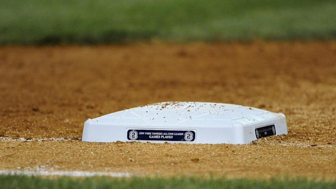 One of the commemorative bases the Yankees are using to honor Derek Jeter during his final home stand positioned at first base during the baseball game between the New York Yankees and the Toronto Blue Jays at Yankee Stadium on Friday, Sept. 19, 2014, in New York. (AP Photo/Kathy Kmonicek)