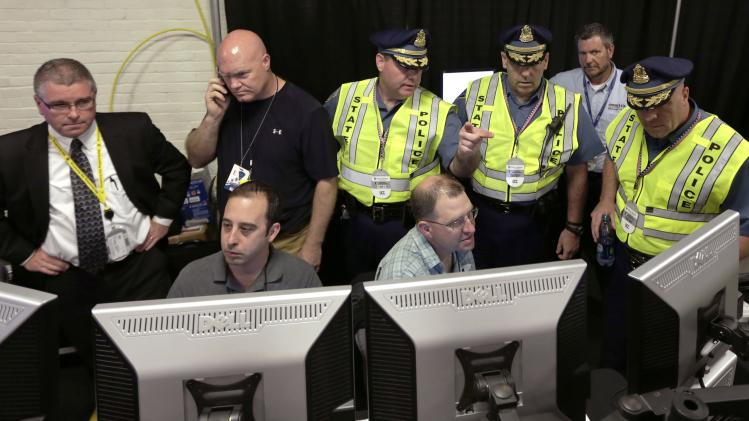Law enforcement officials monitor surveillance cameras as part of an increased security effort for the Independence Day celebration, the first major public gathering since the Boston Marathon bombings, at the Unified Command Center, Wednesday, July 3, 2013, in Boston. The temporary command center combines the control and management of security by local, state and federal law enforcement officals in one location. (AP Photo/Charles Krupa)