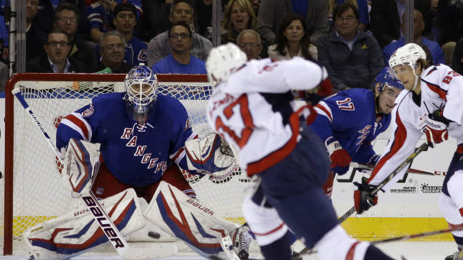 Washington Capitals defenseman Karl Alzner (27) takes a shot as New York Rangers goalie Henrik Lundqvist (30), of Sweden, defends the crease in the second period of Game 3 of their first-round NHL hockey Stanley Cup playoff series in New York, Monday, May 6, 2013. (AP Photo/Kathy Willens)