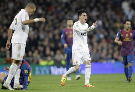 In this photo taken Wednesday Jan. 18, 2012, Real Madrid's Pepe from Portugal, left looks down at F.C. Barcelona's Lionel Messi from Argentina a moment before stamping on his hand as Jose Maria Callejon, centre protests to the referee after receiving a yellow card for his foul on Messi. Real Madrid's coach Jose Mourinho warned Real Madrid defender Pepe could face punishment for stamping on Messi's hand in Wednesday's 2-1 Copa del Rey loss to Barcelona. Pepe has a history of aggressive play in the quot;clasicoquot; series, including a red card in last season's Champions League semifinals, and the hot-tempered Portugal defender stepped on Messi's left hand in the 68th minute of the match. Even Manchester United striker Wayne Rooney tweeted: quot;Pepe. What an idiot. Sometimes people wind u up.quot; (AP Photo/Paul White)