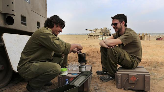 Israeli soldiers prepare coffee at a staging area near the Israel Gaza Strip Border, southern Israel, Thursday, Nov. 22, 2012. A cease-fire agreement between Israel and the Gaza Strip's Hamas rulers took effect Wednesday night, bringing an end to eight days of the fiercest fighting in years and possibly signaling a new era of relations between the bitter enemies. (AP Photo/Tsafrir Abayov)