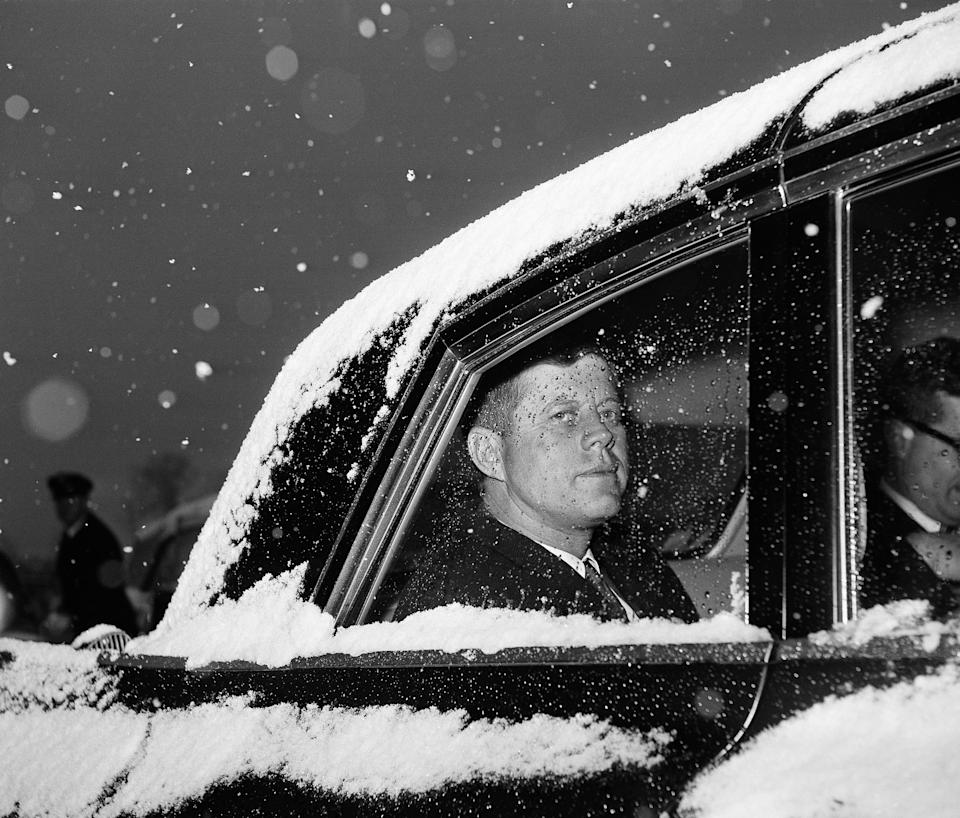 FILE - In this Dec. 9, 1961 file photo, U.S. President John Kennedy looks out of the window from a snow-covered limousine at Andrews Air Force Base, Md. near Washington after his return from Florida. (AP Photo/Byron Rollins)