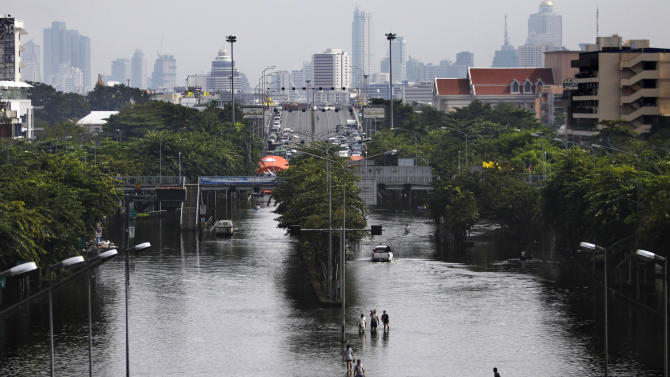 Thai residents wade through a flooded street in Bangkok, Thailand, Saturday, Nov. 5, 2011. Floodwaters lapped Bangkok's largest outdoor market Saturday as officials warned that there were no major barriers between the water and the heart of the Thai capital, less than 6 miles (10 kilometers) away. (AP Photo/Altaf Qadri)
