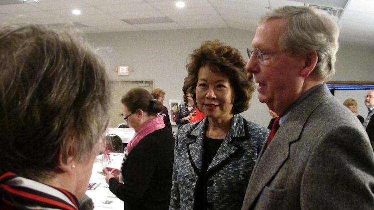 U.S. Sen. Mitch McConnell, right, and his wife, former Labor Secretary Elaine Chao, speak with supporters at a Republican dinner in Winchester, Ky., on Saturday, March 2, 2013. A liberal political group had made an issue of Chao's ethnicity in messages distributed on Twitter earlier this month.  (AP Photo/Roger Alford)