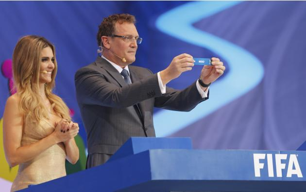 "Valcke holds up the slip showing ""Mexico"" during the draw for the 2014 World Cup in Sao Joao da Mata"