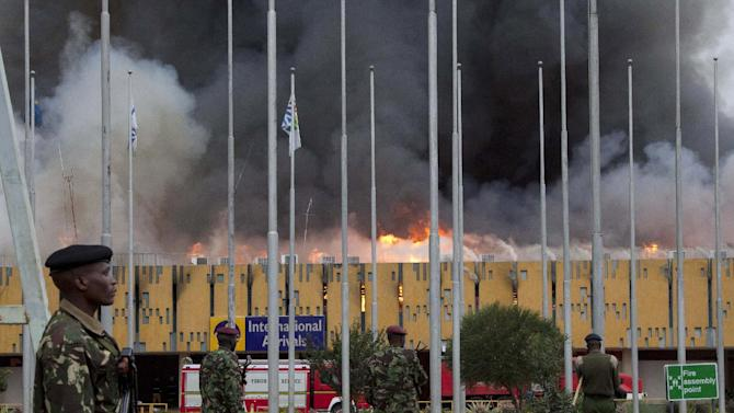 ALTERNATIVE CROP - Police stand guard as fire engulfs the International arrivals unit of Jomo Kenyatta International Airport, Nairobi, Kenya, Wednesday Aug. 7, 2013. The fire engulfed the arrivals hall at Kenya's main international airport early Wednesday, forcing East Africa's largest airport to close and the rerouting of all inbound flights. Dark black smoke that billowed skyward was visible across much of Nairobi as emergency teams battled the blaze. (AP Photo/Sayyid Azim)