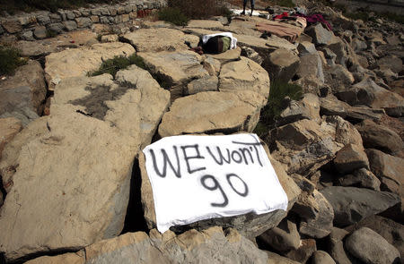 "A migrant rests near a banner that reads ""We won't go"" on the rocks of  the seawall at the Saint Ludovic border crossing on the Mediterranean Sea between Vintimille and Menton"