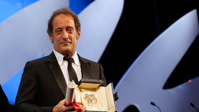 French actor Vincent Lindon poses on stage after being awarded with the Best Actor prize during the closing ceremony of the 68th Cannes Film Festival in Cannes, France, on May 24, 2015