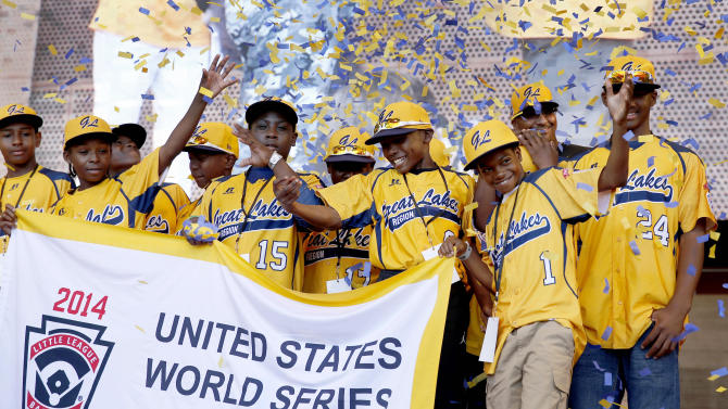FILE - In this Aug. 27, 2014, file photo, members of the Jackie Robinson West All Stars Little League baseball team participate in a rally in Chicago celebrating the team's U.S. Little League Championship. In a lawsuit filed Thursday, Feb. 11, 2016, in Chicago's Cook County Circuit Court, the parents of 13 members of the Chicago Little League team stripped last year of its 2014 U.S. championship are suing team officials, Little League Baseball, an ESPN sportscaster and the man who exposed the team's residency violations. (AP Photo/Charles Rex Arbogast, File)