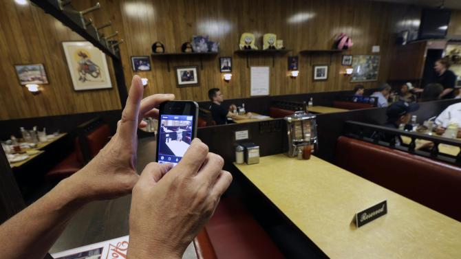 """Liz O'Neil, of Montclair, N.J., takes a photograph of a reserved booth where the last show of the HBO series """"The Sopranos"""" was filmed at Holsten's ice cream parlor, Wednesday, June 19, 2013, in Bloomfield, N.J. The sign was put on the booth where the last scene was filmed in honor of actor James Gandolfini who died Wednesday in Italy. He was 51. (AP Photo/Julio Cortez)"""