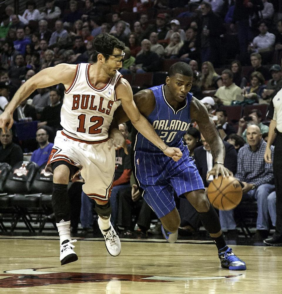 Chicago Bulls' Kirk Hinrich, left, tries to keep up with Orlando Magic's DeQuan Jones during the first quarter of an NBA basketball game in Chicago on Tuesday, Nov. 6, 2012. (AP Photo/Charles Cherney)