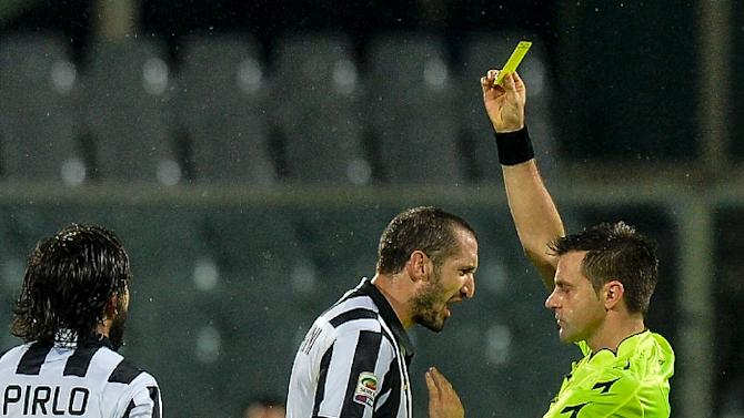 Nicola Rizzoli (right) shows a yellow card to Juventus defender Giorgio Chiellini during a match against Fiorentina on December 5, 2014 in Florence